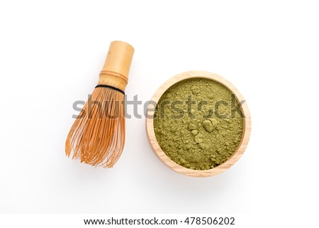 powder green tea and bamboo whisk on white background