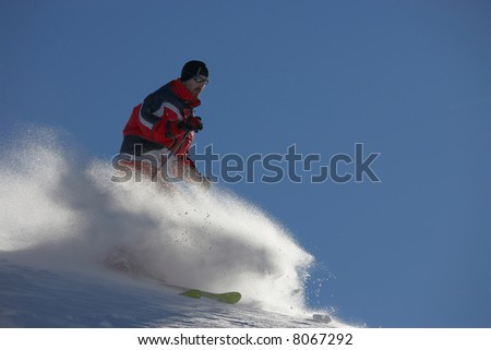 powder skiing in front of blue sky