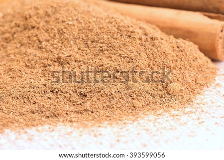 Powdered cinnamon and sticks on wooden plate