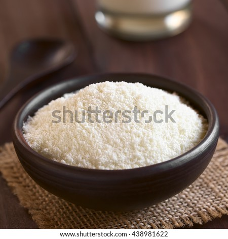 Powdered or dried milk in small bowl, photographed on dark wood with natural light (Selective Focus, Focus in the middle of the image) - stock photo