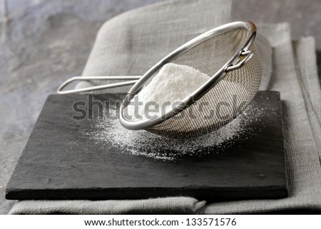 powdered sugar in a metal strainer on a gray background - stock photo