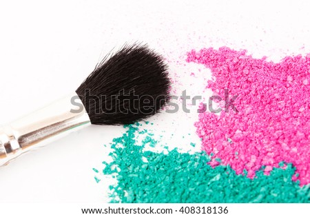 Powdery eyeshadow makeup and brush on a white background