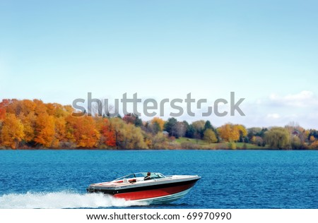 power boating on an autumn lake - stock photo