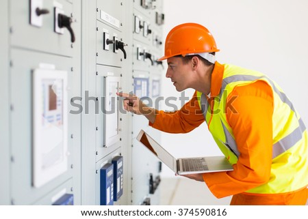 power company technical worker using laptop computer in control room - stock photo