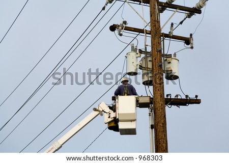 Power company worker wearing a hardhat is repairing electrical wires from a utility bucket truck. - stock photo