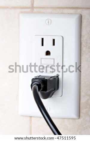 Power cord plugged in a wall socket - stock photo