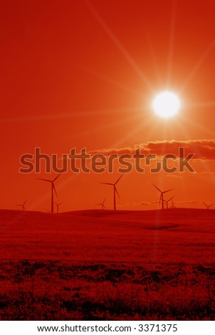 Power Generating Wind Turbines in Stylized Red Against Blazing Sun