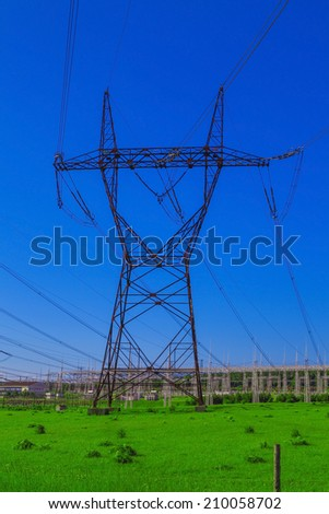 Power line in the middle of a green field with blue sky