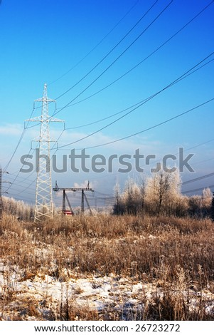 Power line pylons in a winter forest - stock photo