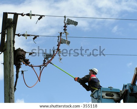 Power lineman closing switch on high voltage line - stock photo