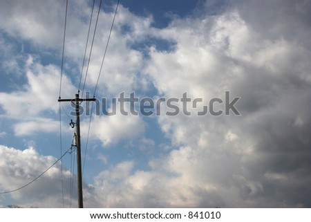 Power lines against blue sky and clouds.