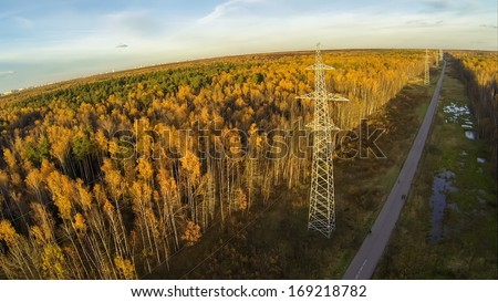 Power lines among the road and trees with colorful foliage in park on Elk island at Moscow, view from unmanned quadrocopter. - stock photo