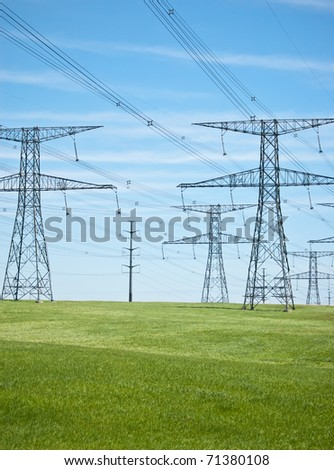 Power lines and pylons running across a green field with blue sky in the background. - stock photo