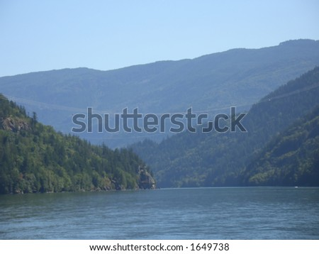 Power lines crossing the river - stock photo