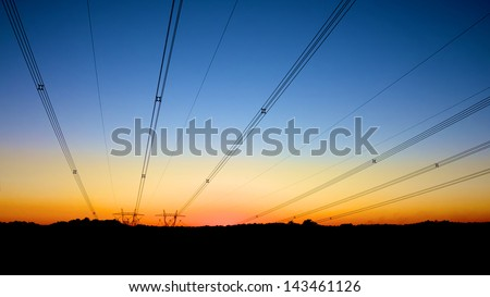 Power lines delivering electricity from a distance - stock photo