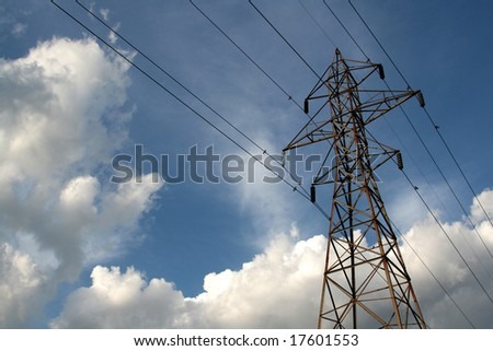 Power lines lit by the sun with blue sky and clouds in the background. - stock photo