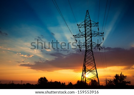Power lines on a colorful sunrise - stock photo