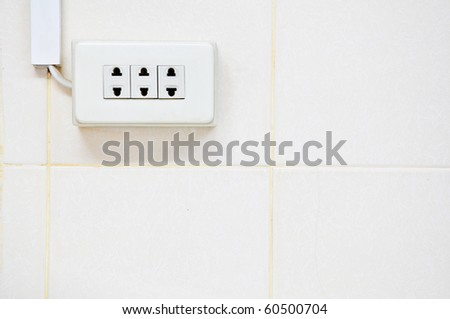 Power outlet on ceramic wall - stock photo