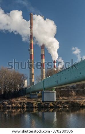 Power plant and overhead pipeline at cold morning over Vistula river, Krakow, Poland