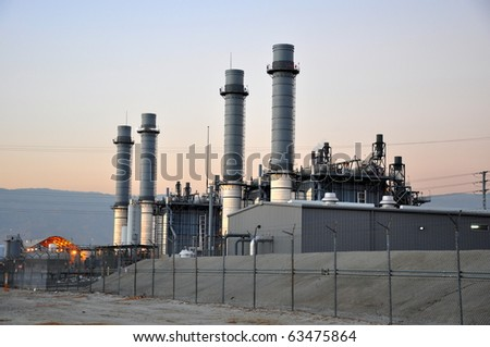 Power plant at dusk with lights shining - stock photo