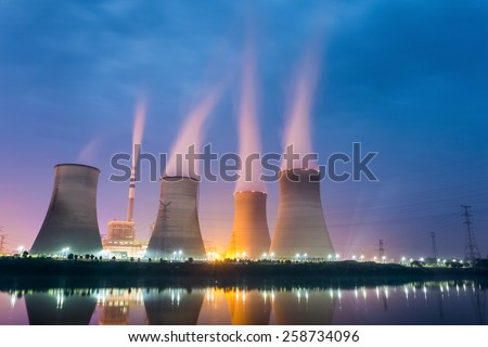 power plant at night , cooling tower closeup with steam - stock photo