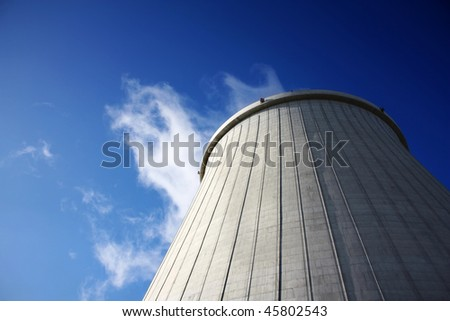 Power plant big chimney producing white smoke against a blue sky - stock photo