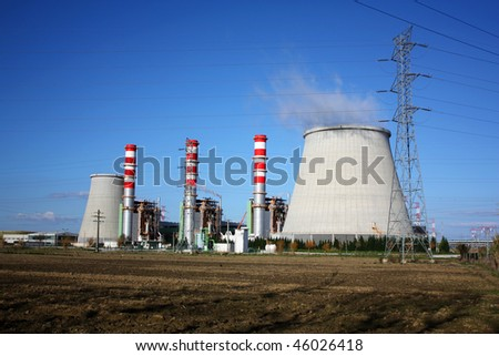 Power plant chimneys producing white smoke against a blue sky - stock photo