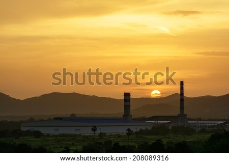 Power plant factory silhouette over sunset