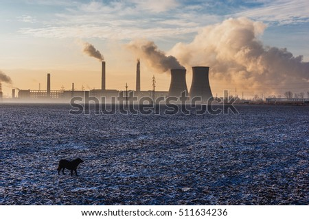 Power plant or refinery in the countryside with chimneys billowing clouds of smoke, pollution concept.