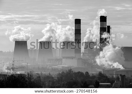 Power plant pipes with swirling smoke at sunrise, environmental pollution, monochrome picture  - stock photo