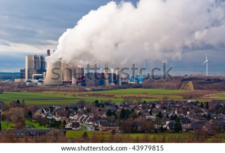 Power plant, wind turbine and small town in Germany - stock photo