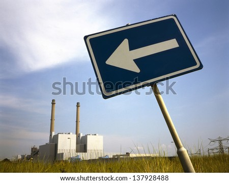Power plant with arrow sign against cloudy blue sky