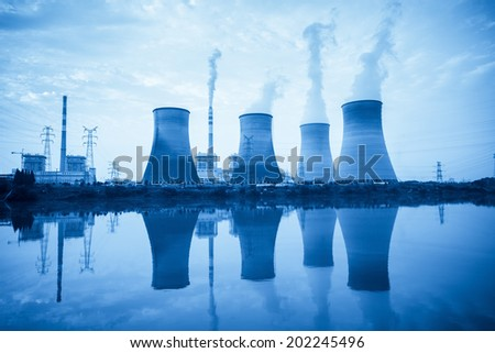 power plant with cooling towers and reflection in the river   - stock photo