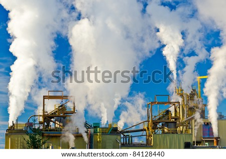 Power plants generating smokes at sunrise - stock photo