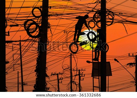 Power pole with Tangle of Electrical wires with two technician repairing during sunset sky. - stock photo