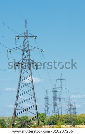 Power poles.  Row of numerous high-voltage, heavy-duty industrial pylons for electricity distribution. Parallel wires on a blue sky background. Power, energy and electricity infrastructure concept. - stock photo