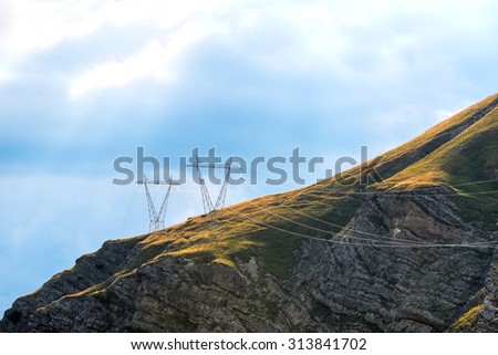 Power pylons in the mountains - stock photo
