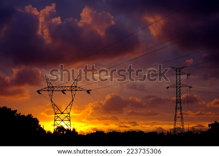 Power pylons over a fantastic sunset sky. - stock photo