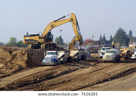 Power shovel loads trucks on site of new highway construction