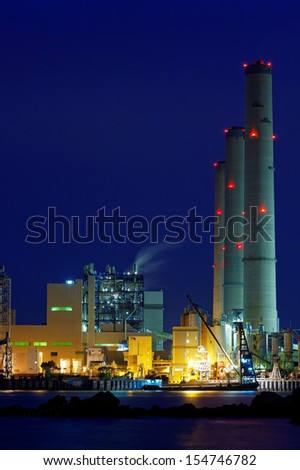 power station at night with smoke  - stock photo