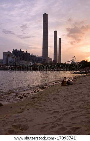 Power station at sunset beach in foreground - stock photo