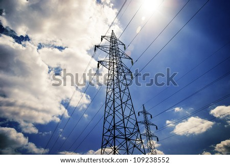 Power towers with blue sky and clouds - stock photo