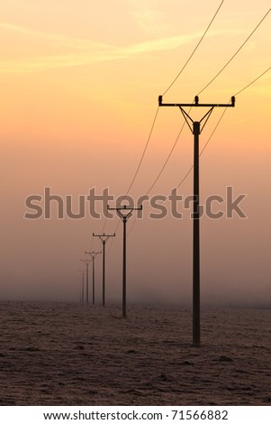 Power-transmission pole in the mist in winter nature - stock photo