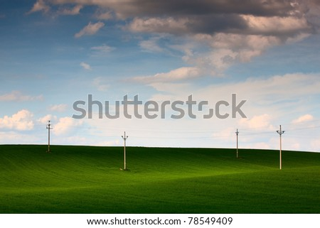 Power-transmission poles on the empty field in spring - stock photo