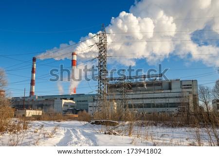 power transmission tower on   background smoking chimneys - stock photo