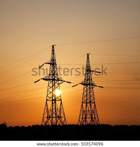 Power transmission towers in the background of the sunset sky - stock photo