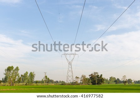 Power transmission towers in the rice fields. Power transmission towers from power plants through the rice fields. - stock photo