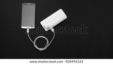 Powerbank charging smartphone on blackboard - stock photo