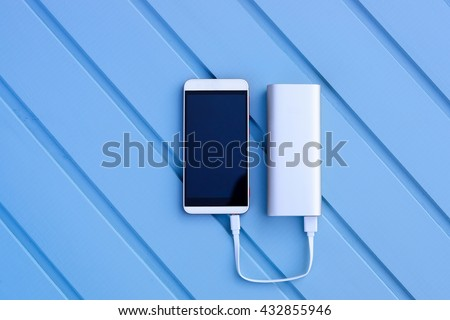 Powerbank charging smartphone - outdoor, blue wooden background