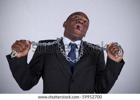 Powerful african businessman with a steel chain in his hands - stock photo